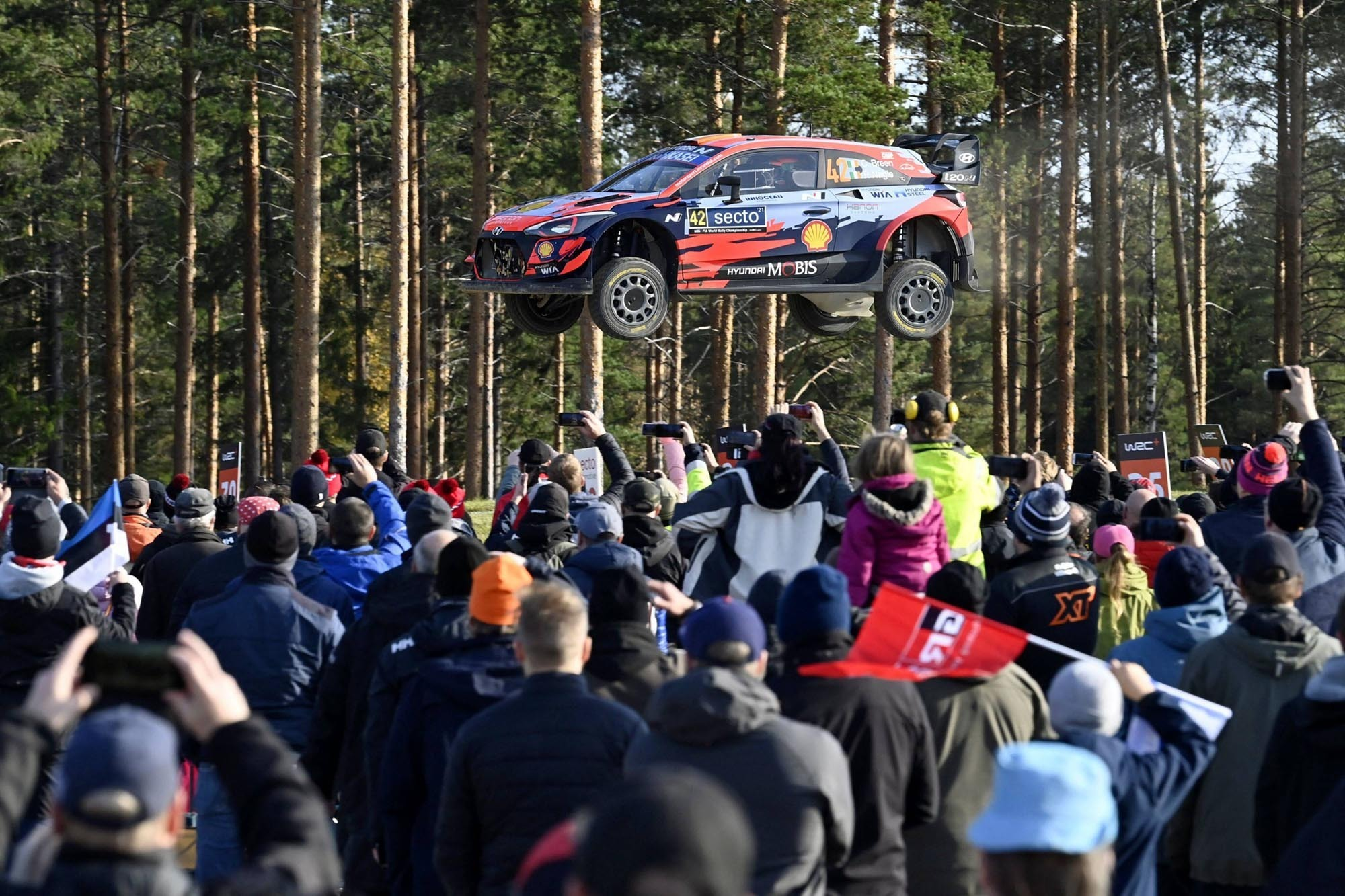 Spectators watch as the Hyundai of Irish driver Craig Breen and his Irish co-driver Paul Nagle soars through the air during the special stage 19, Ruuhimaki, at the WRC Rally Finland in Laukaa, Finland, on October 3, 2021.